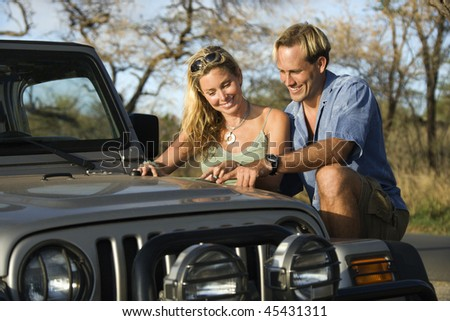 A smiling man and woman look at a map spread out on the hood of a car. Horizontal format.