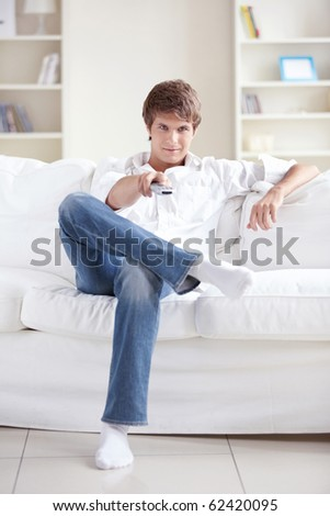 A smiling man changes channels control - stock photo