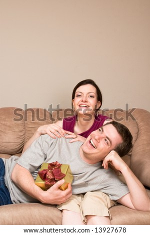 A smiling man holding a gift box lying on a smiling woman's lap on sofa.  Vertically framed shot. - stock photo