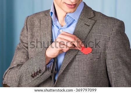 A smiling man in a jacket with a red heart on the hand on blue wall background. The young man, a guy with a red heart. Valentine's Day, give love. - stock photo