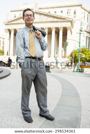 A smiling man in a suit stands with his jacket over  his shoulder and hand in his pocket. A stately building with columns is in the background. - stock photo