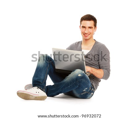 A smiling man sitting on the floor with a laptop, isolated on white background - stock photo