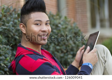 A smiling man using a tablet computer outdoors.