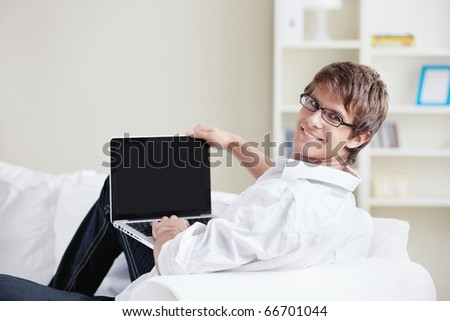 A smiling man with a laptop looks back - stock photo