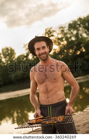 A smiling man with hat and beard is holding the barbecue grill. He is standing shirtless in the sand at the beach with his swimsuit. He has prepared nice meat kebabs at the fire for the dinner. - stock photo