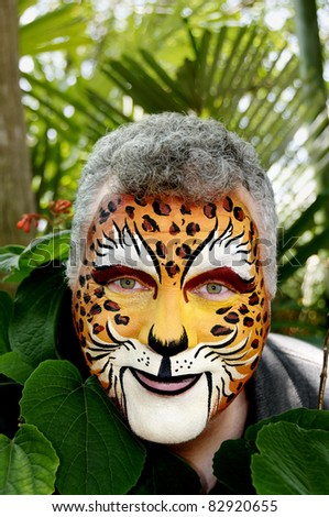 A smiling man with his face painted to look like a leopard. - stock photo