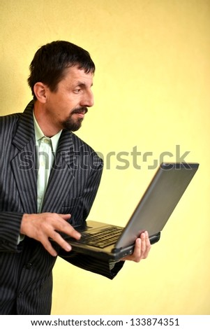 A smiling man with laptop outdoor