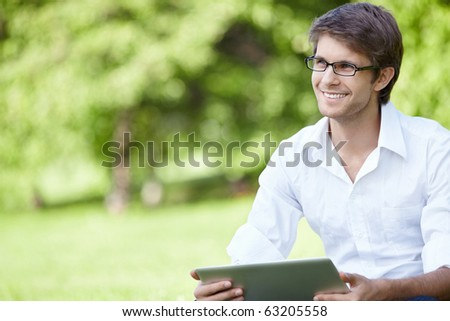A smiling man with laptop outdoor - stock photo