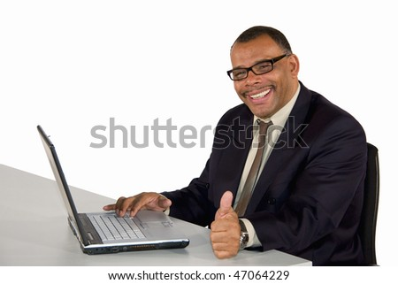 a smiling mature African-American businessman with a laptop posing with the thumbs up sign, isolated on white background - stock photo