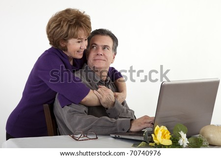 A smiling mature couple sitting at a computer. - stock photo