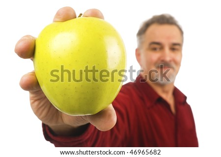 A smiling, mature man with a beard holds out an apple for all to see. - stock photo