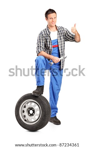 A smiling mechanic giving a thumb up with a spare tire and wrench isolated on white background - stock photo