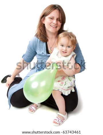 A smiling mother sits with her daughter on her knee.  The little girl is playing with a green balloon.