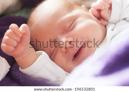 A smiling newborn baby laying on a blancet.Picture is toned. - stock photo