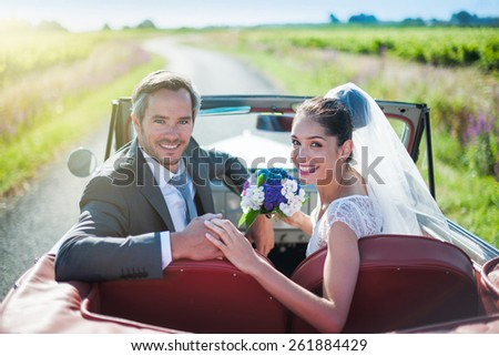 A smiling newlywed couple is holding hands and looking at camera in a retro car. - stock photo