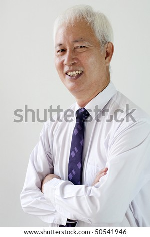 a smiling old asian ethnic businessman with plain background - stock photo