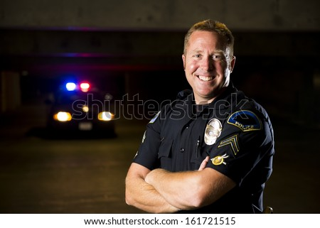 A smiling police officer with his patrol car in the background. - stock photo
