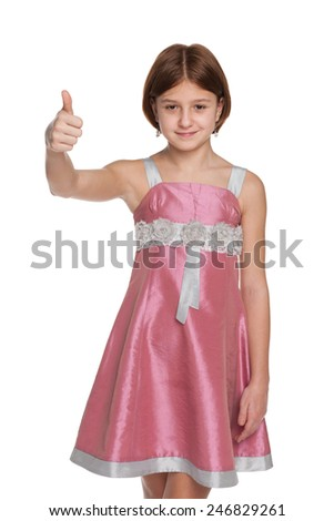 A smiling preteen girl holds her thumb up on the white background