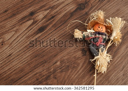 A smiling scarecrow isolated against a wooden background