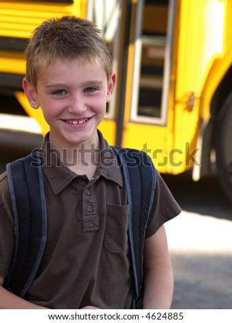 a smiling school boy with a yellow school bus in the background - stock photo
