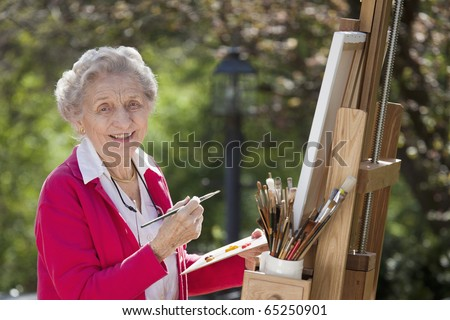 A smiling senior woman is in an outdoor setting painting. Horizontal shot.
