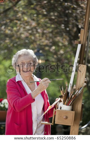 A smiling senior woman is in an outdoor setting painting. Vertical shot. - stock photo