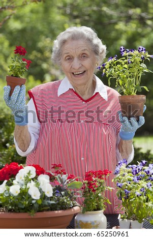 A smiling senior woman is standing in front of a table with potted flowers on a table.  She is holding a starter plant she is getting ready to pot. Vertical shot.