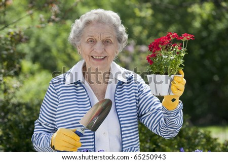 A smiling senior woman is standing with a trowel and holding a starter plant she is getting ready to plant. Horizontal shot. - stock photo