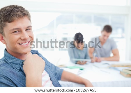 A smiling student looking into the camera with his hand near his neck as his friends sit behind him - stock photo