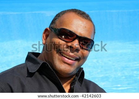 a smiling, successful and happy African-American man with sunglasses photographed in the summer sun in his garden sitting at his swimming pool - stock photo