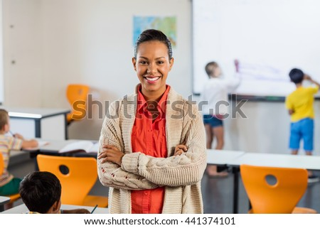A smiling teacher posing for the camera in classroom - stock photo