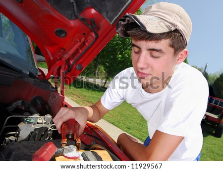 A smiling teenage boy working on a truck engine. - stock photo