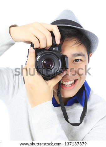 A smiling teenager holding a camera. Readable logos removed.  - stock photo