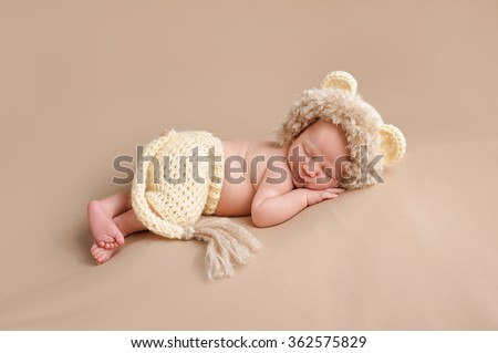A smiling three week old newborn baby boy wearing a crocheted lion costume. Shot in the studio on a khaki colored background. - stock photo