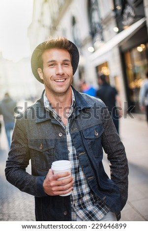 a smiling trendy guy with a hat, walking in the city a cup of coffee in hand - stock photo