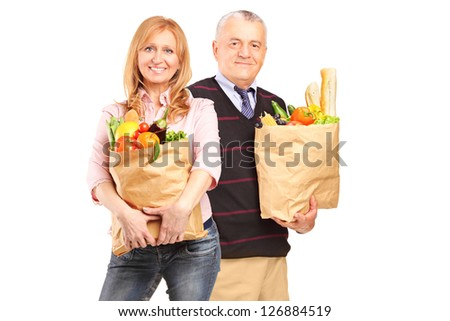 A smiling woman and gentleman holding a paper bag full of groceries isolated on white background