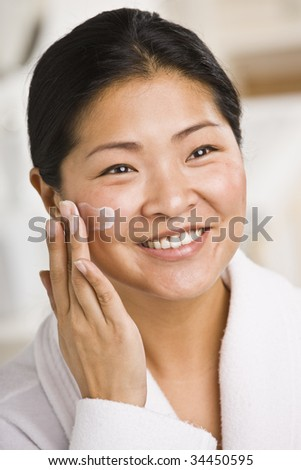 A smiling woman applies facial cream.  She is looking away from the camera.  Vertically framed shot. - stock photo