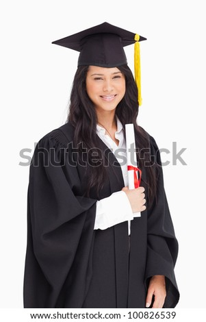 A smiling woman having graduated from university with a degree in her hands