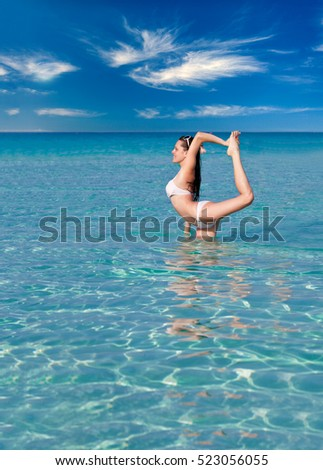 A smiling woman is doing flexibility exercise in the sea
