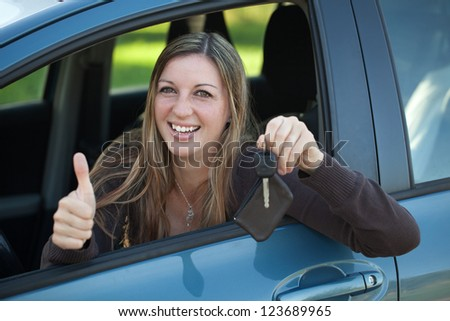 A smiling woman is leaning out of the window and showing a key - stock photo