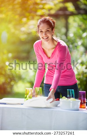 A smiling woman is looking at camera while setting the table in the garden for her family - stock photo