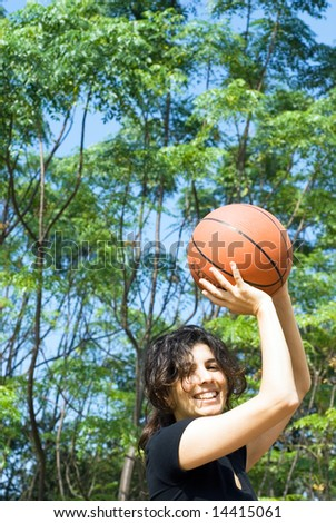 A smiling woman is playing basketball on a court at the park.  The woman is looking at the camera and about to make a shot.  Vertically framed photo. - stock photo