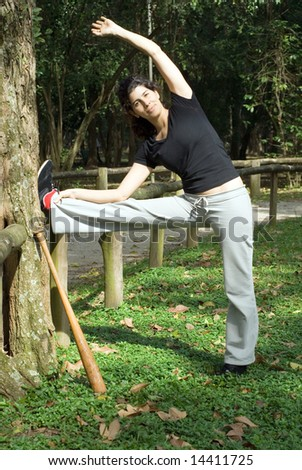 A smiling woman is standing next to a tree.  She is looking at the camera and stretching.  There is a baseball bat leaning against the tree.  Vertically framed photo. - stock photo
