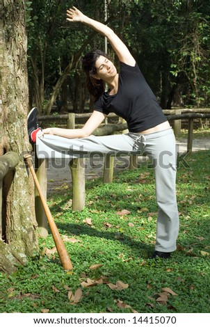 A smiling woman is standing next to a tree.  She is looking away from the camera and stretching.  There is a baseball bat leaning against the tree.  Vertically framed photo. - stock photo