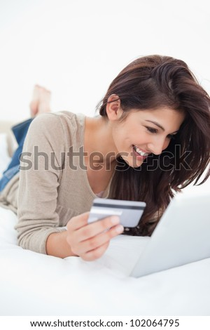 A smiling woman lying on the bed as she uses her credit card on her tablet.