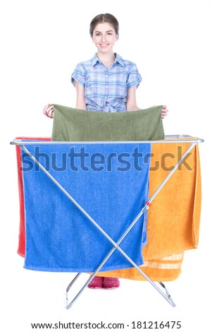 A smiling woman putting towels to dry. Isolated on white background - stock photo