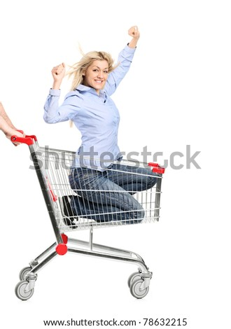 A smiling woman riding in a shopping cart isolated on white background - stock photo
