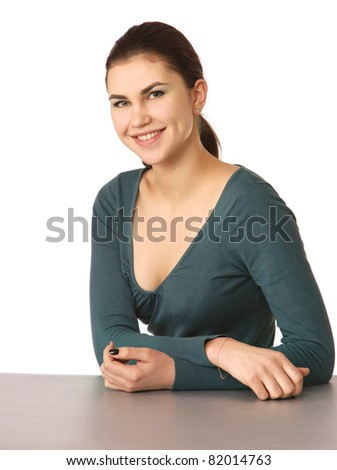 A smiling woman sitting at the desk, isolated on white - stock photo
