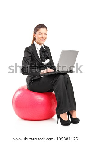 A smiling woman sitting on a pilates ball and working on a notebook computer isolated against white background - stock photo