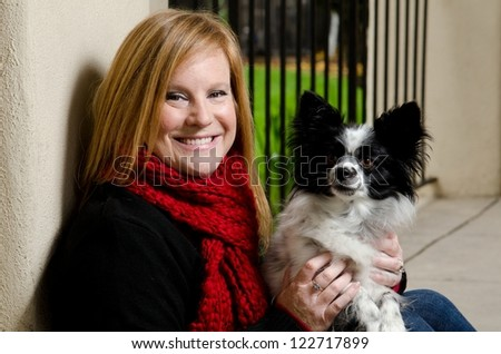 a smiling woman wearing a red scarf with a papillon dog. - stock photo